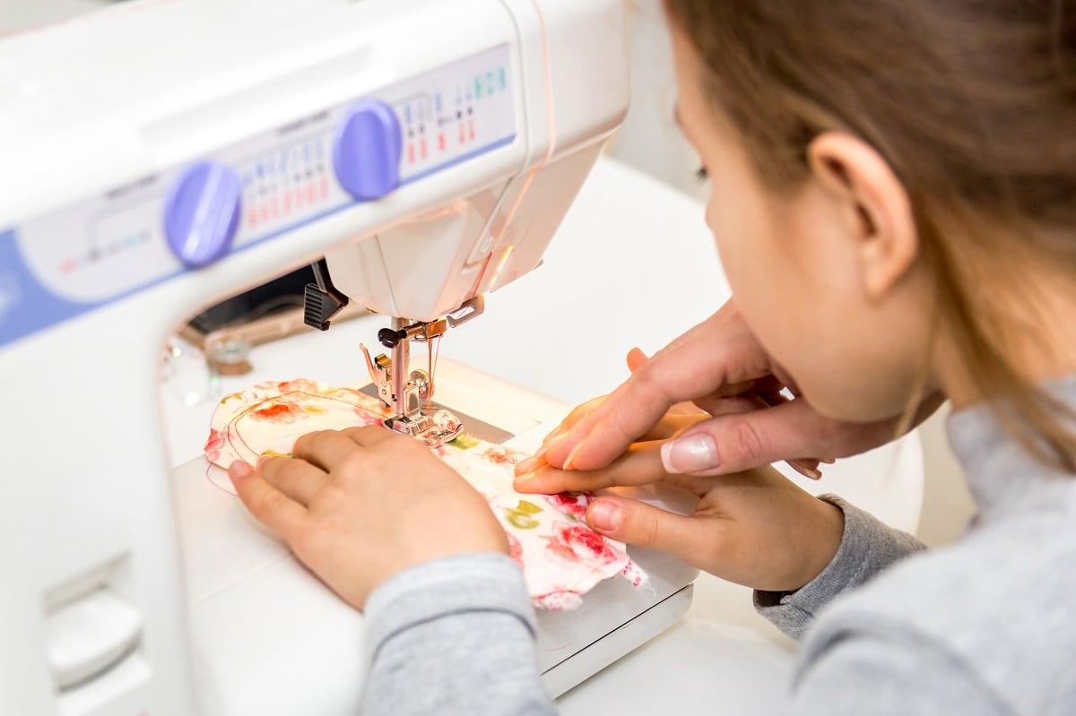 enfant qui apprend à coudre à le machine à coudre